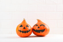 Pumpkins With Painted Faces On A Colored Background For Halloween.