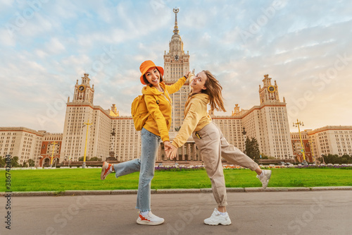 Obraz Two female friends students on the background of the building of Moscow University. Education, tourism and holiday concept - fototapety do salonu