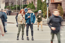 Full Length Shot Of Two Teenagers Totally Absorbed In Their Smartphones, Ignoring Each Other While Standing Together On The City Street