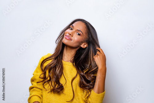 Portrait of beautiful black woman in yellow sweater with long curly hair