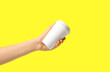 Leinwandbild Motiv Woman holding takeaway paper coffee cup on yellow background, closeup