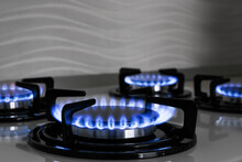 Modern Gas Cooktop With Burning Blue Flames In Kitchen