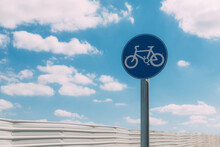 Close-up View Of Round Blue And White Bicycle Lane Sign Against A Fence And Blue Sky With Clouds. Outdoor Sign. Traffic Laws. One Circle Road Sign On A Pillar. Street Signs. Safe Bike Ride.