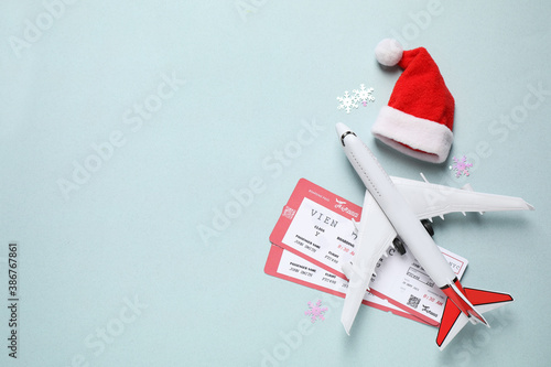 Santa hat, toy airplane and airline tickets on light blue background, space for text. Christmas vacation