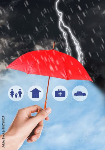 Obraz Insurance concept. Woman protecting illustrations with red umbrella from storm, closeup - fototapety do salonu