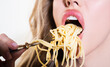 Close up sexy lips with noodles pasta. Female mouth eat spaghetti.