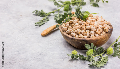 Fotografia Dry chickpeas or garbanzo beans in wooden  bowl, healthy food ingredient