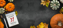 Autumn Decoration With Pumpkins And Colorful Leaves And Tear-off Calendar With Message OCTOBER 31st HALLOWEEN 2020 On Chalkboard Background