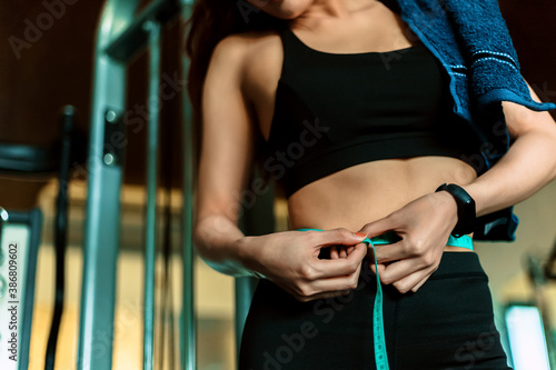 Obraz Athletic slim woman measuring her waist by measure tape after workout and exercise in gym. - fototapety do salonu
