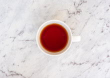 High Angle View Of Rooibos Tea In White Cup On Grey. Marbled Benchtop (selective Focus)
