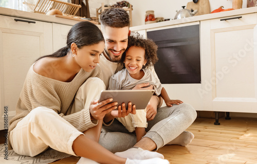 happy multi ethnic family: parents and son using tablet  at home - 386815468