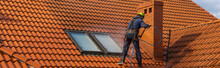 High-altitude Worker Washing The Roof With Pressurized Water