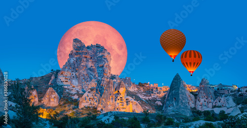 "Hot air balloon flying over Uchisar castle with full moon ""Elements of this image furnished by NASA """