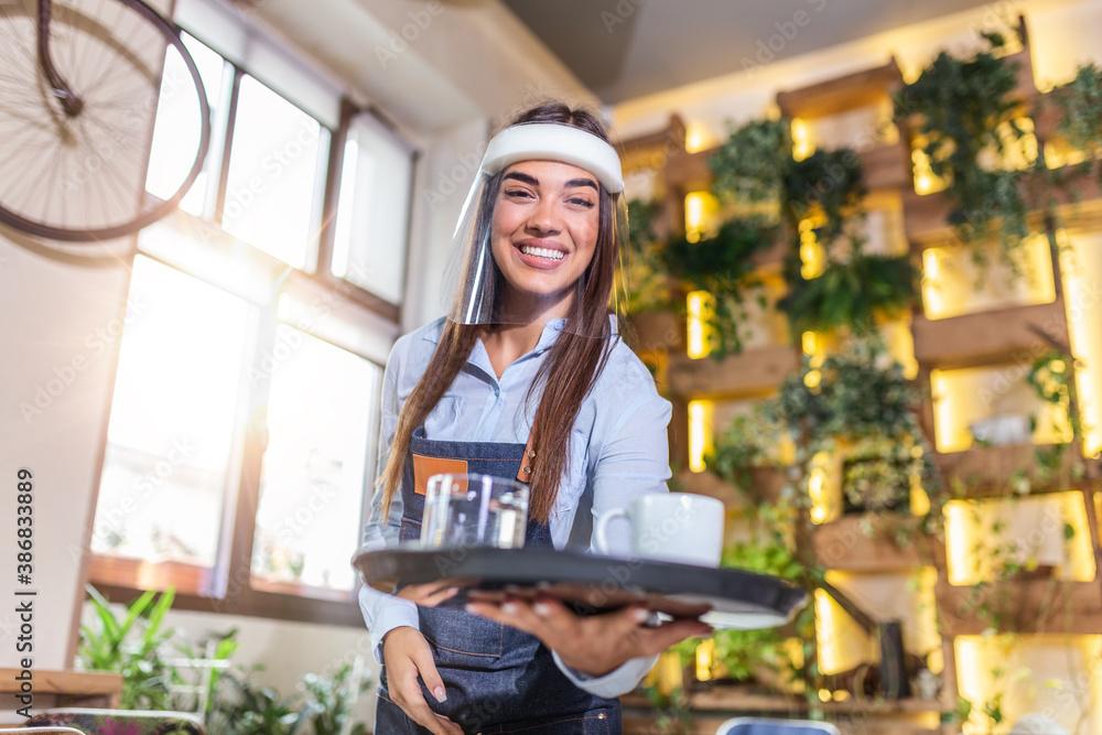 Fototapeta Female waitress wearing face shield, visor serves the coffee in restaurant during coronavirus pandemic representing new normal concept