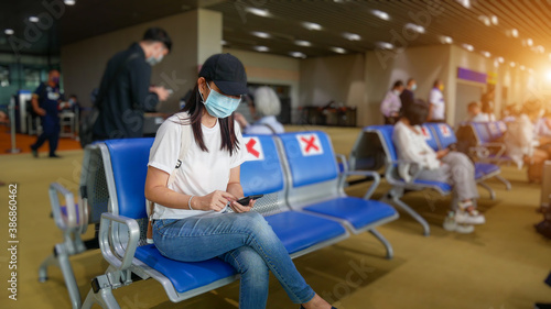 Obraz Asian tourist with mobile phone ,wearing hygienic mask, sit on chair with social distancing to prevent pandemic during travel at airport terminal. new normal after coronavirus, covid-19 virus epidemic - fototapety do salonu