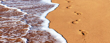 Close-up Of The Sea Coast, Clear Sea Water With Shallow Waves And White Foam Washes The Shore With A Smooth Brown Sandy Surface And Footprints Of Bare Human Feet