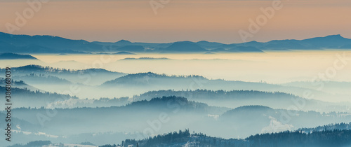 Amazing mountain scenery with hills and mist from Barania Gora hill in Beskid Slaski mountains in Poland