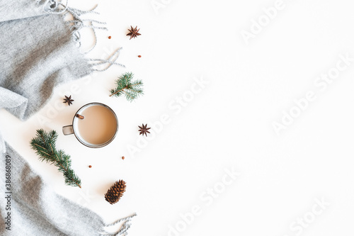 Obraz Christmas composition. Cup of coffee, fir tree branches, plaid on white background. Christmas, winter, new year concept. Flat lay, top view - fototapety do salonu