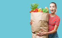 Cheerful Young Woman Holding A Grocery Bag Filled With Vegetable