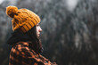 Side view of thoughtful young woman wearing plaid shirt and yellow winter hat looking at view in cold weather conditions. Travel, outdoor and cold weather concept. Copy Space