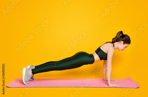 Obraz Profile side full body view of nice slender perfect shaped sportive girl trainer instructor doing push-ups isolated on bright yellow color background - fototapety do salonu