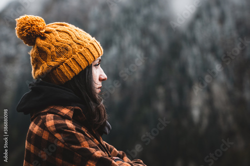 Photo Side view of thoughtful young woman wearing plaid shirt and yellow winter hat looking at view in cold weather conditions