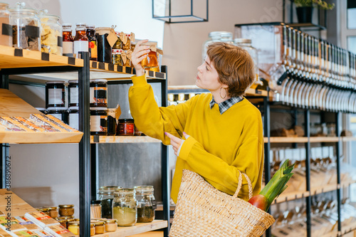 Fototapeta Minimalist vegan style girl with wicker bag and reusable glass coffee cup on background of interior of zero waste shop
