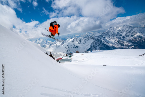 Fotografia, Obraz Professional athlete skier freerider in an orange suit with a backpack flies in
