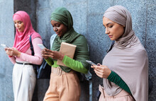 Modern Arab Ladies Using Smartphones Standing Over Gray Wall