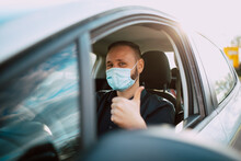 A Portrait Of A Handsome Caucasian Businessman In A Black Shirt With A Face Mask Giving A Thumbs Up While Driving A Car On The Way To Work. Protection During The COVID - 19 Coronavirus Pandemic
