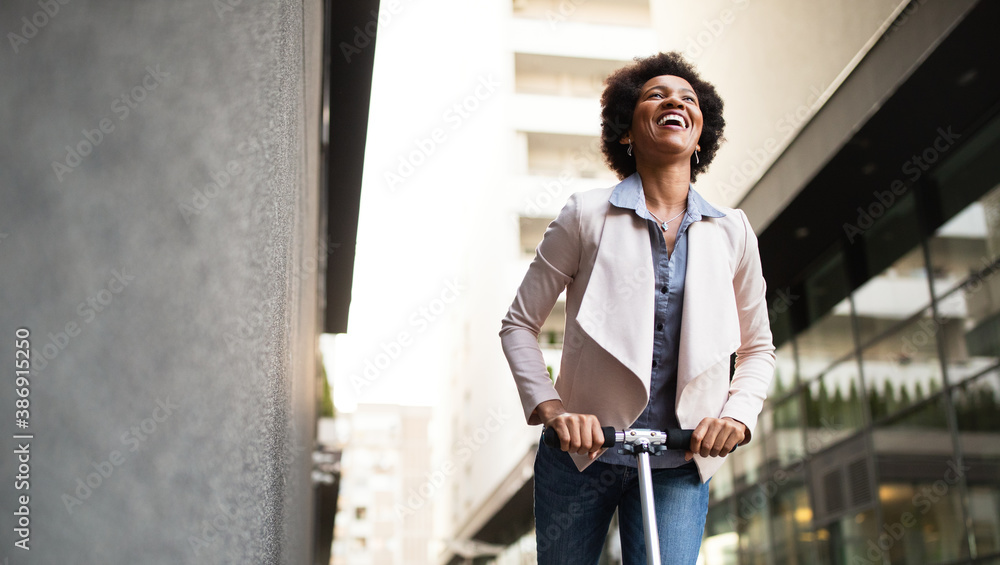 Fototapeta Happy woman on the electric scooter with background of office building