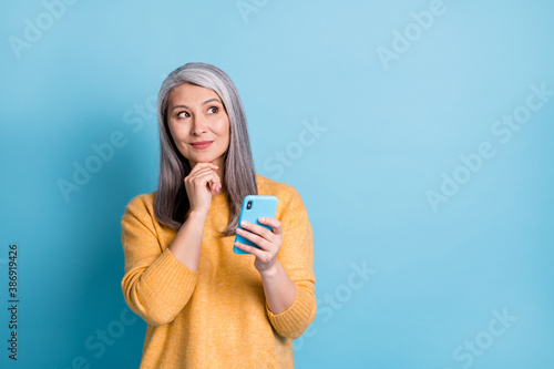 Photo of minded old woman use smartphone look copyspace touch fingers chin think thoughts decide texting typing chatting wear style stylish sweater isolated blue color background
