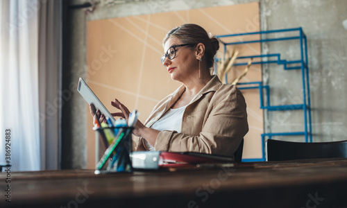 Caucasian senior woman with glasses is using a tablet during a busy working day from home