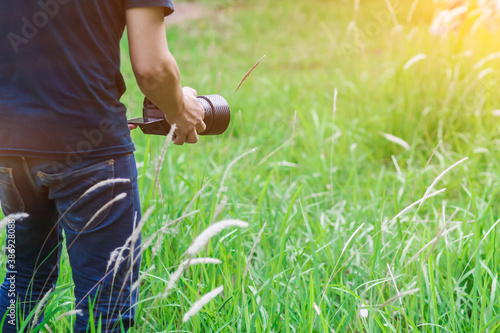 Foto Soft Light and Blurred image, A photographer capturing the beautiful Grass flowers in the evening with a DSLR camera, photographers walking to capture the grass flowers in the beautiful grass alone