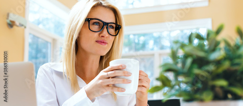 Fototapeta Happy young woman drinking coffee in an office obraz