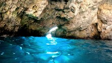 Cavern Over Turquoise Water With A Hole In Which Overexposed Light Enters And Illuminate The Water.