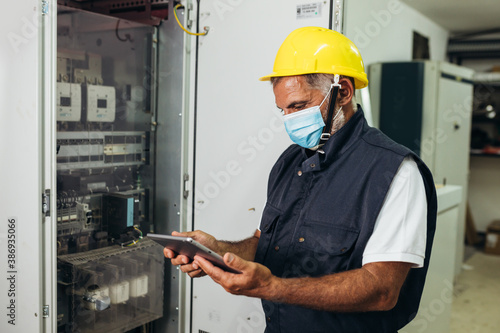 Obraz na plátne engineer wearing covid protective mask checking the electrical cabinet at contro