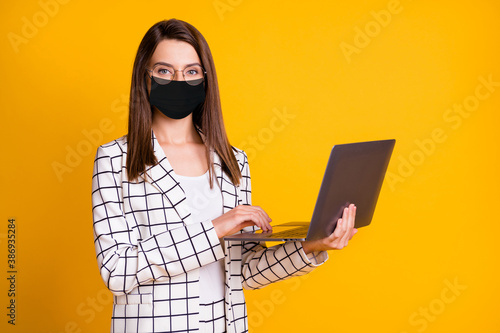 Photo portrait of pretty woman keeping laptop wearing black face mask smiling isolated on bright yellow color background - 386935284