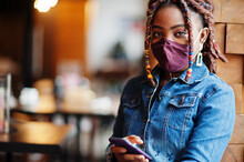 Stylish African American Woman With Dreadlocks Afro Hair, Wear Jeans Jacket And Face Protect  Mask At Restaurant, Hold Cellphone. New Normal Life After Coronavirus Epidemic.