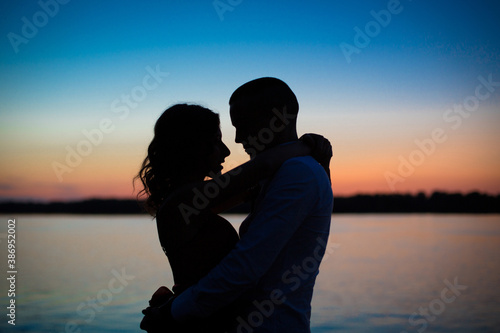 Fotomural Silhouettes of a couple in love romance at sunset