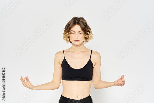 Obraz sporty woman in black jeans and a t-shirt doing exercises in a bright room - fototapety do salonu