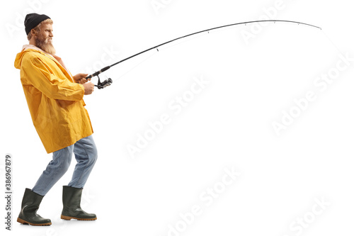 Fototapeta Full length profile shot of a young bearded fisherman catching with a fishing po