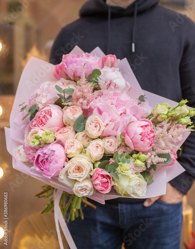 Young man holding big beautiful blossoming bouquet in pink color of fresh flowers wrapped in pink paper. © Liudmyla