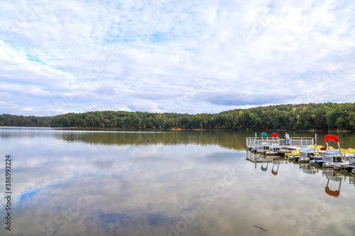 colorful boats at the dock in the middle of the lake with lush green and autumn Fototapete
