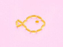Yellow Omega 3 Capsules With Fish Oil On A Pink Background