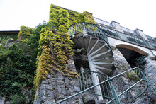 Spiral Staircase Outside A Stone Building Covered With Vegetation