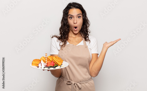 Fototapeta young hispanic woman looking surprised and shocked, with jaw dropped holding an object with an open hand on the side obraz