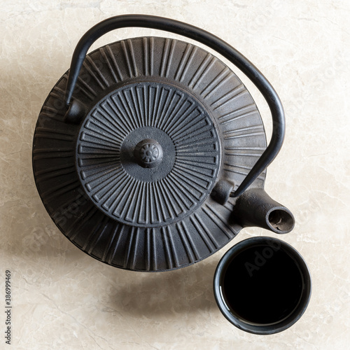 Fototapeta Top view of iron cast teapot and traditional clay tea cup filled with black tea obraz na płótnie