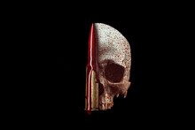 Bloody Human Skull Isolated On Black Background . Still Life Blood And Bullet. Copy Space.