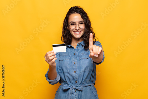 Obraz young hispanic woman smiling and looking friendly, showing number one or first with hand forward, counting down - fototapety do salonu